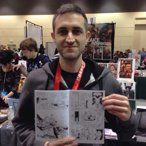 Tyrell holds up a page he drew in issue 5.
